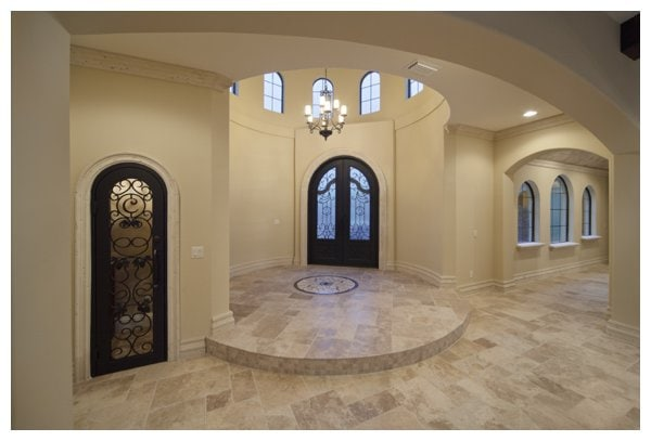 The tower entry leads to a circular foyer crowned by arched windows to infuse plenty of natural light in Villa Capzolli, designed and built by Orlando Custom Home Builder Jorge Ulibarri.