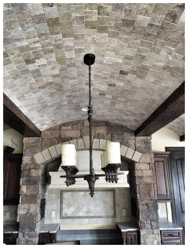 A stone and beam barrel ceiling adds curves to soften the rusticity of this Tuscan-inspired kitchen in a home under construction by Orlando Custom Home Builder Jorge Ulibarri. For more information, go to www.imyourbuidler.com
