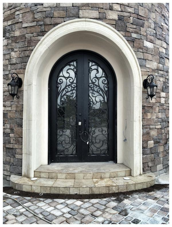Detail shot of the precast arch that frames the double-entry wrought-iron door in this Windermere home by Orlando Custom Home Builder Jorge Ulibarri. For more, go to www.imyourbuilder.com