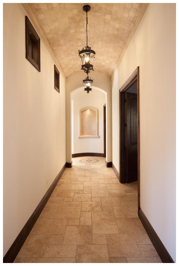 The main hallway downstairs features a barrel ceiling of travertine stone and leads to the master suite and guest suite in Villa Hernandez.  Orlando Custom Home Builder Jorge Ulibarri built the home in Acuera, a gated enclave in Seminole County, Florida for a client.  For more, go to www.imyourbuilder.com