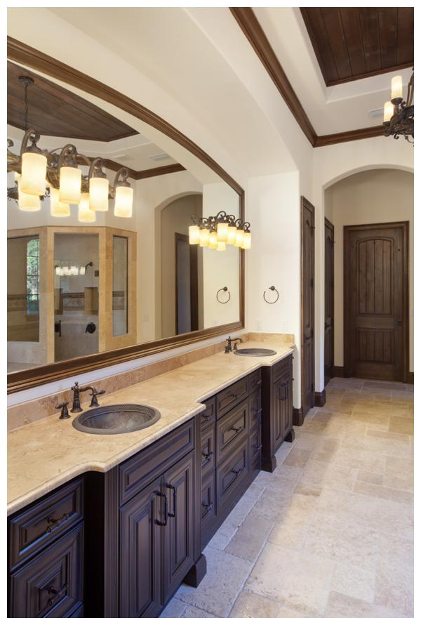The master bathroom in Villa Hernandez features a wood plank ceiling framed by dark trim and a stately iron chandelier.