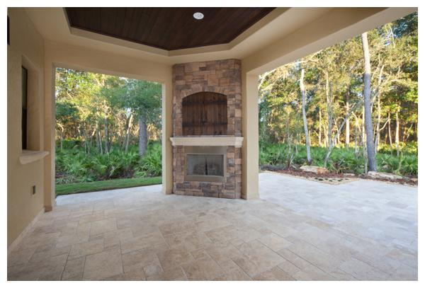 The outdoor living room of Villa Hernandez overlooks a nature preserve and sets the scene for entertaining al fresco with a stacked stone fireplace and barn-door TV niche. Orlando Custom Home Builder Jorge Ulibarri built the 6,300 square foot home in Acuera, a gated enclave in Seminole County Florida.  For more go to www.imyourbuilder.com
