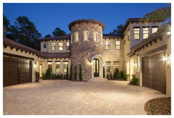 The stone tower of Villa Hernandez adds elegant curb appeal in perfect sync with the home's natural surroundings. Precast stone frames the tower windows and the custom made wrought iron door. Orlando Custom Home Builder Jorge Ulibarri built the home for a client who wanted a Mediterranean style home with warmth and timeless appeal.  For more go to www.imyourbuilder.com