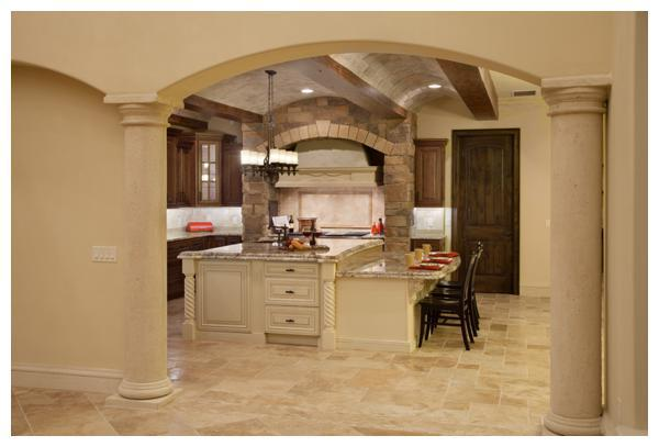Villa Verona's Tuscan-style kitchen with travertine stone and wood beam barrel ceiling and stone niche framing the precast stone range hood with an oversized bi-level kitchen island that serves as both a food prep area and breakfast bar. The home was built by Orlando Custom Home Builder Jorge Ulibarri www.ImYourBuilder.com