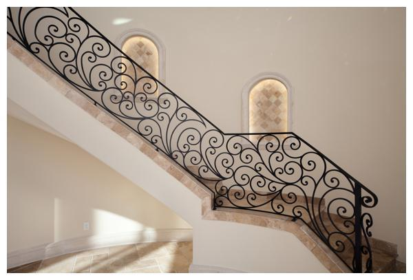 Detailed scrollwork embellishes the railings visible throughout the home. The hand crafted intricate design took four months to create. Notice the niches built into the wall of the stairway. These niches required special engineering because they are built inside of the load bearing tower wall. Villa Verona was