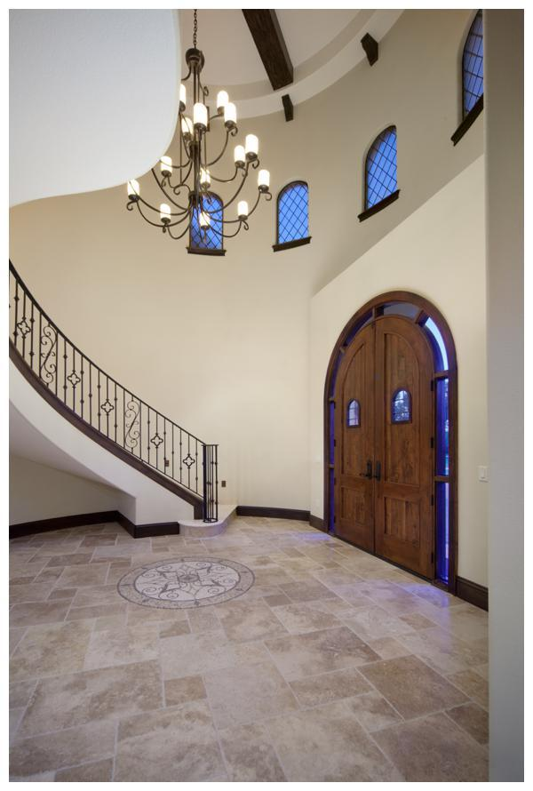 The front door to the tower entry is crafted of solid distressed wood giving this 6,300 square foot home by Orlando Custom Home Builder Jorge Ulibarri curb appeal and Old World character. Two wrought iron embellished windows and a window arch infuse the space with natural light. A mosaic stone floor medallion adds to the grand entry and centers below a massive wrought iron chandelier. Photo Credit: Harvey Smith