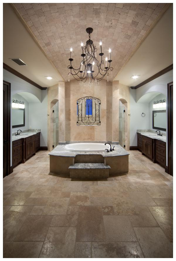 The master bath in this 6,300 square foot custom home by Orlando Custom Home Builder Jorge Ulibarri features a barrel ceiling punctuated by an elegant wrought iron and crystal chandelier with a soaking tub that shares a wall with a shower on the other side built for two. The double entry shower features a wrought iron window overlooking the soaking tub. The master bath exudes Old World elegance with generous use of stone. Photo credit: Harvey Smith
