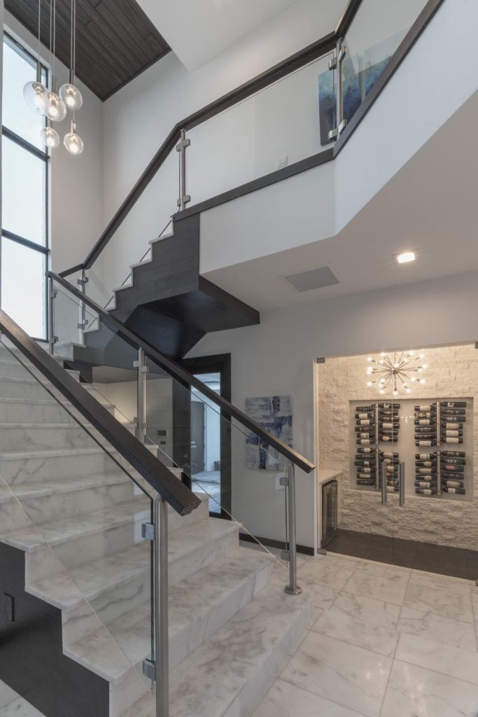 A glass panel staircase framed with chrome supports and wood railings with marble stairs in this Florida Modern Home designed and built by Orlando Custom Home Builder Jorge Ulibarri www.imyourbuilder.com