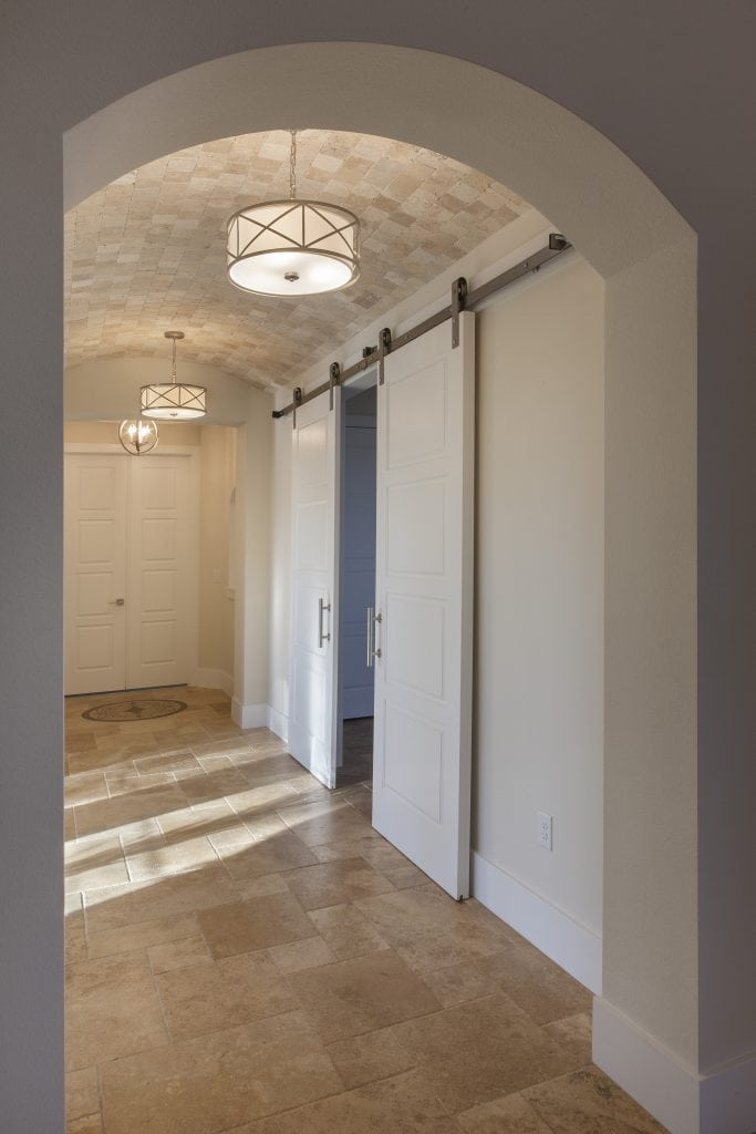 Barn doors painted white with stainless steel hardware open to the media room and the hallway with a barrel travertine tile ceiling. The home was designed and built by Orlando Custom Home Builder Jorge Ulibarri. www.imyourbuilder.com