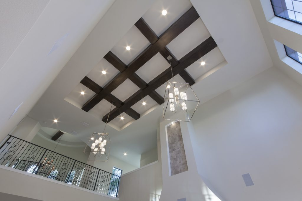 The ceiling treatment in the grand room draws the eye up to the grid of beams and two geometric chandeliers, an open hallway bridges the two wings of the home upstairs overlooking the tower entry and grand room. The home was designed and built by Orlando Custom Home Builder Jorge Ulibarri. www.imyourbuilder.com