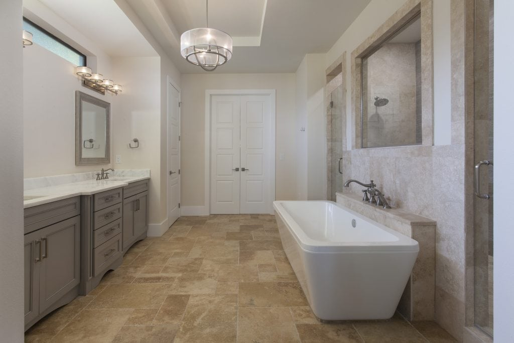 The masterbath features a free standing tub that fronts a double-entry shower with gray base cabinets and white and gray granite countertops in this custom home designed and built by Orlando Luxury Home Builder Jorge Ulibarri. www.imyourbuilder.com