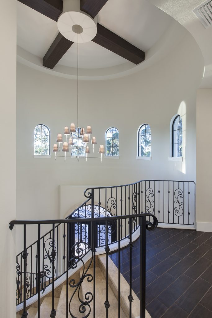 A two-story tower foyer makes a grand entrance pouring in natural light from a crown of windows. The wrought iron staircase echoes the design of the custom made wrought iron and glass door in this home designed and built by Orlando Custom Home Builder Jorge Ulibarri. www.imyourbuilder.com