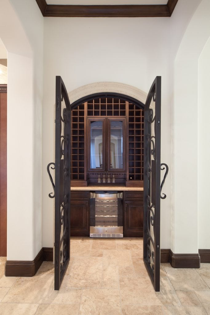 Traditional wine room designed and built by Orlando Custom Home Builder Jorge Ulibarri, owner of Cornerstone Custom Construction. The wine room features custom made wrought iron doors and wine refrigeration.