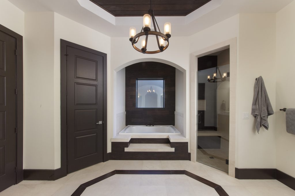 Master Bathroom in Villa Sirena, a home by Orlando Custom Home Builder Jorge Ulibarri mixes wood-looking tile with natural wood ceilings, white quartz counters and espresso wood cabinets for a warm contemporary look.
