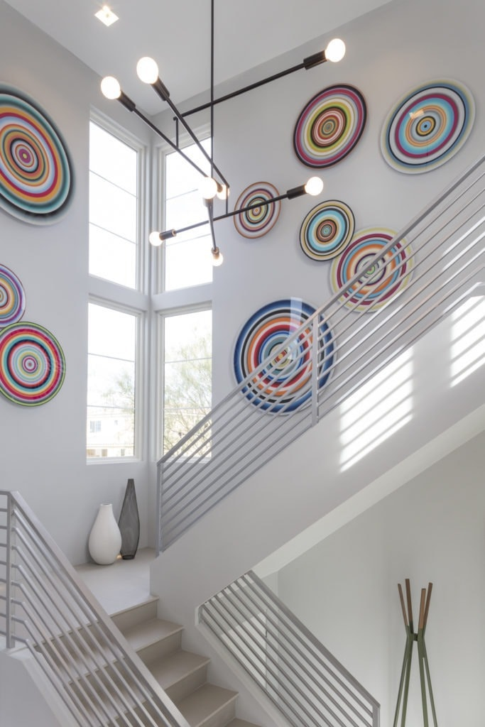 This metal contemporary staircase makes a sculptural statement accented with glass art on the walls in this home. For more design ideas by Orlando Custom Home Builder go to www.cornerstonecustomconstruction.com