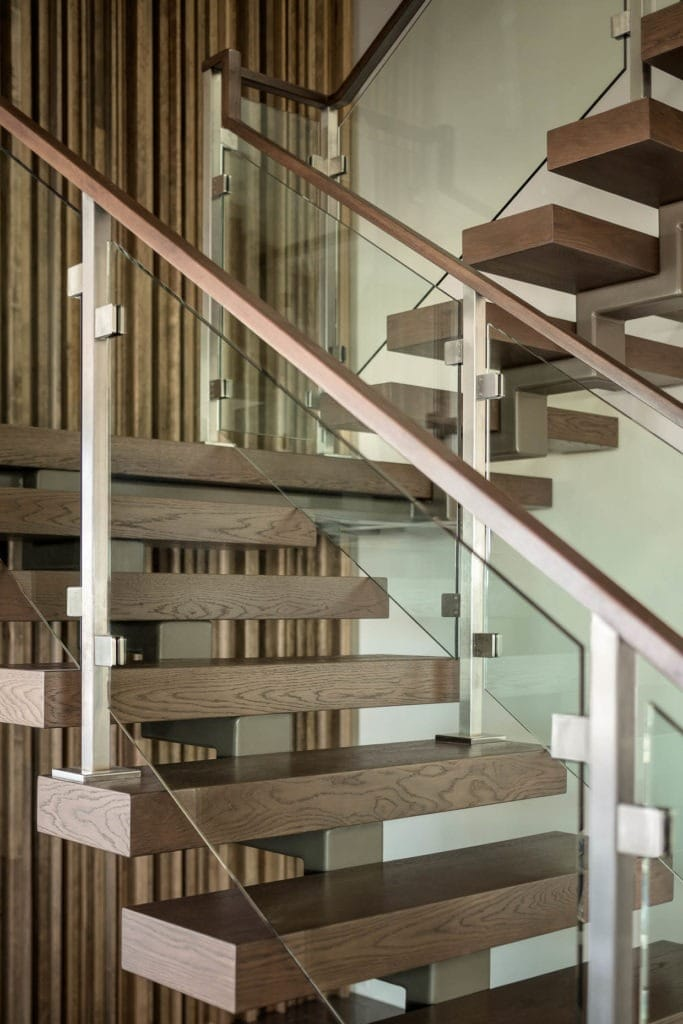 Floating wood stair treads and acrylic panels with wood hand rails mix materials as an architectural feature in this home. For more design ideas by Orlando Custom Home Builder go to www.cornerstonecustomconstruction.com