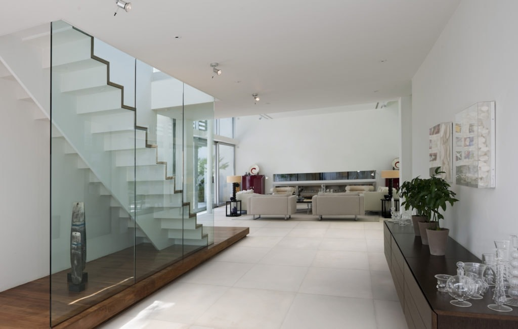 This floating staircase is encased in a glass wall that negates the need for hand railings. For more design ideas by Orlando Custom Home Builder go to www.cornerstonecustomconstruction.com