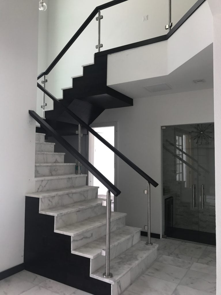 This staircase blends the natural materials of marble and wood with glass and chrome for a perfect balance of warmth with sleek elements. The staircase was designed by Orlando Custom Home Builder Jorge Ulibarri in this Florida Modern home under construction in Lake Mary. www.imyourbuilder.com