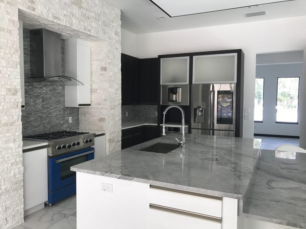 In this Florida-Modern kitchen designed and built by Orlando Custom Homebuilder Jorge Ulibarri, white ledge stone frames the custom-colored blue range, drawing attention to the pop of color. for more go to www.imyourbuilder.com