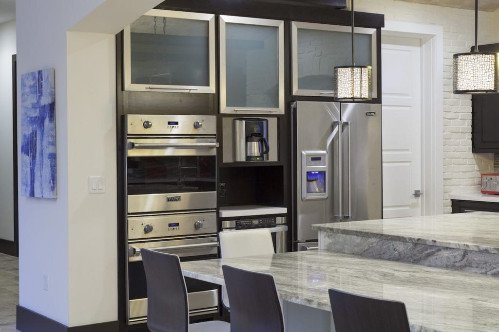 The appliance wall in this transitional style kitchen by Orlando Custom HomeBuilder Jorge Ulibarri showcases sleek stainless steel appliances accented with glass fronted and chrome framed upper cabinets for a modern edge. www.imyourbuilder.com