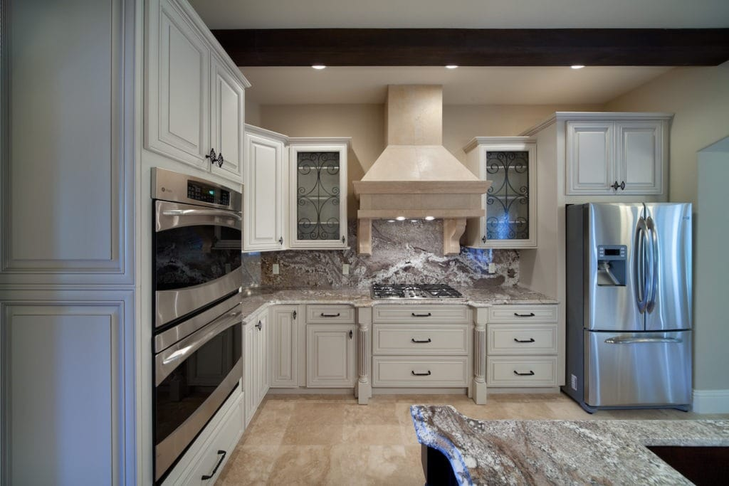 A transitional style kitchen designed and built by Orlando Custom HomeBuilder Jorge Ulibarri that skews traditional with ornate cabinetry, travertine floors and wood beams. The white cabinets and stainless appliances temper the traditional elements. www.imyourbuilder.com