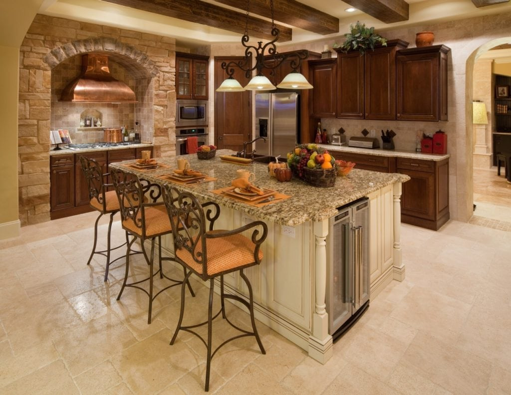 This traditional style kitchen pulls from Tuscan influences such as the copper rangehood framed by stone and kitchen island base cabinetry that mimics furniture with wood carvings and embellishments. www.imyourbuilder.com