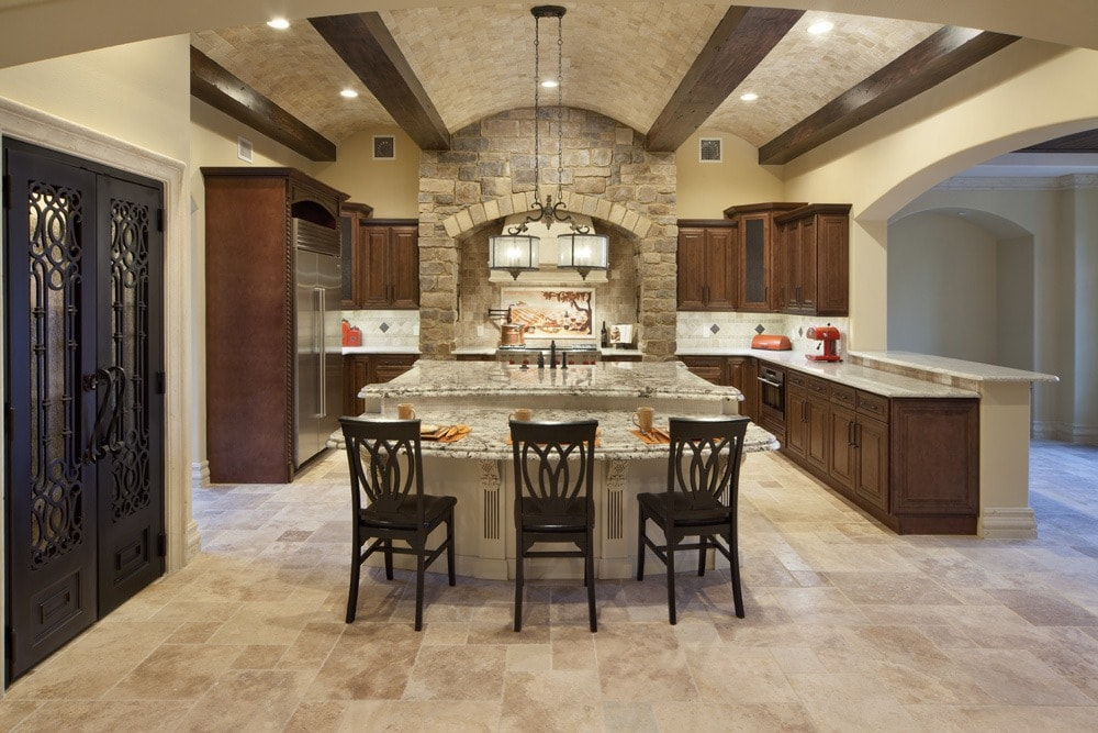 A traditional style kitchen designed and built by Orlando Custom HomeBuilder Jorge Ulibarri showcases an undulating barrel and beam ceiling crafted of travertine tiles and wood beams. The wrought iron double door pantry is another focal point. www.imyourbuilder.com