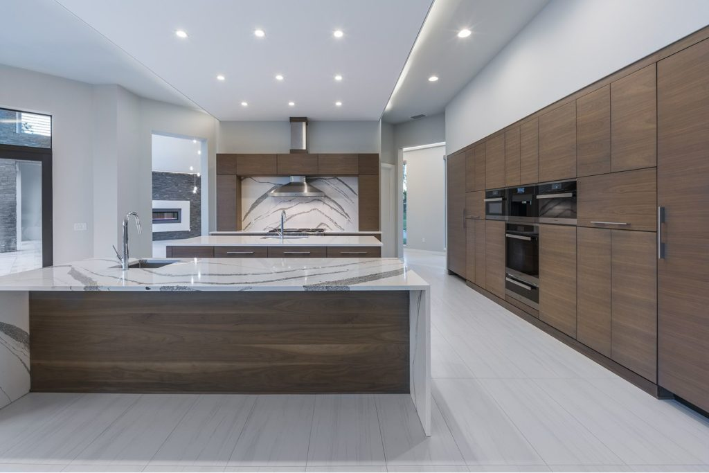 Contemporary kitchen well-appointed with two islands with quartz countertops in this Florida Modern home by Orlando Custom Homebuilder Jorge Ulibarri