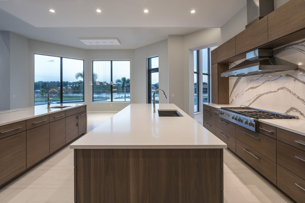 The kitchen backsplash crafted of white quartz with gray veining echoes the wraparound countertop of the island facing the great room in this Florida Modern home by Orlando Custom Homebuilder Jorge Ulibarri