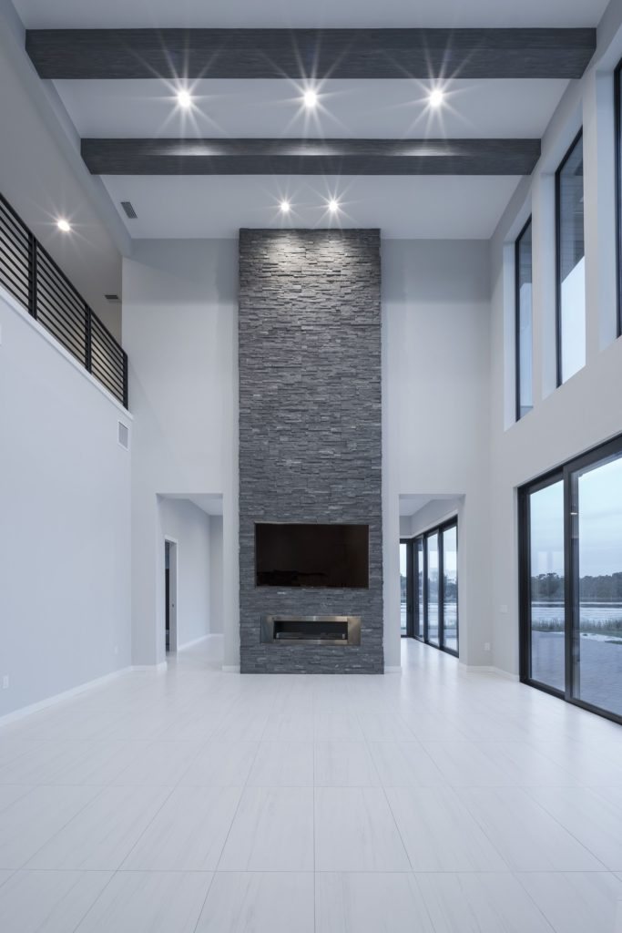 The great room opens to the kitchen and draws focus to a floor-to-ceiling wall of ledgestone that frames a fireplace and TV screen in this Florida Modern home by Orlando Custom Homebuilder Jorge Ulibarri