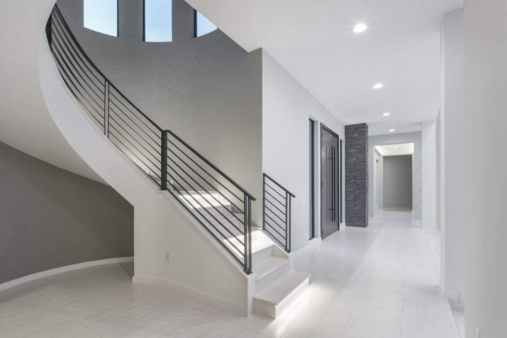 The black wrought iron staircase is crafted to coordinate with the black wrought iron flat panel double entry front door in this Florida Modern home by Orlando Custom Homebuilder Jorge Ulibarri