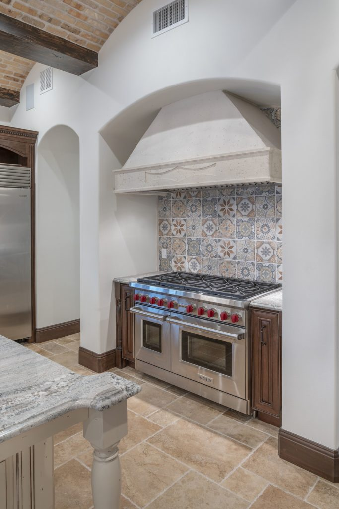 A custom range hood crafted of precast stone coordinates with handpainted tiles on the backsplash of the range niche in this Spanish Revival Custom Home by Orlando Custom Homebuilder Jorge Ulibarri.