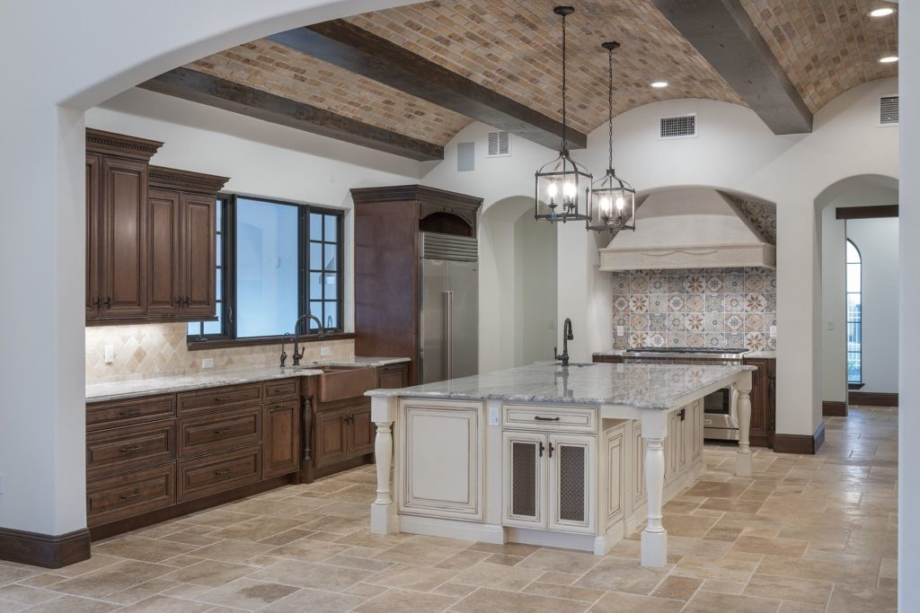 The granite island counter and granite perimeter counters with gray and white veining contrast with walnut wood stained cabinetry and travertine floors and backsplashes to give this kitchen its Spanish Revival style in this custom home by Orlando custom homebuilder Jorge Ulibarri.