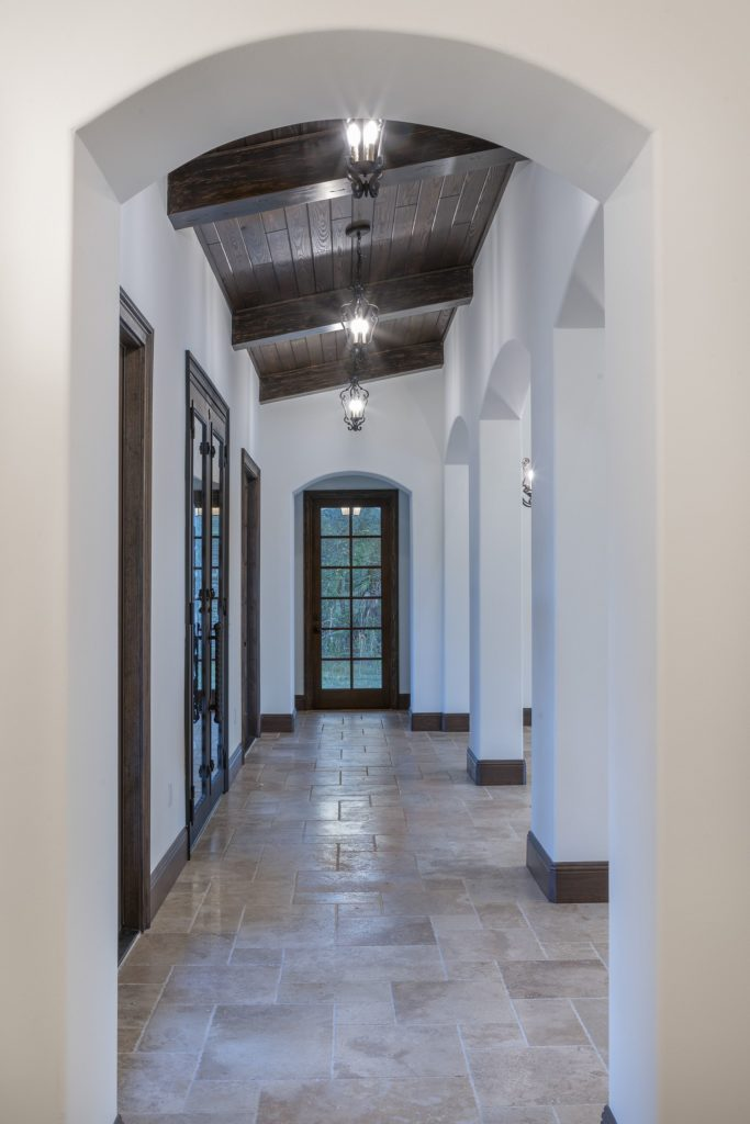 Interior hallway with arches that open to the great room in this Spanish Revival custom home by Orlando Custom Homebuilder Jorge Ulibarri.
