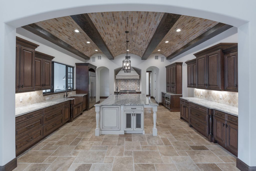 The kitchen opens to the great room and features a brick and beam barrel ceiling with a contrasting ivory colored island and handpainted tile backsplash in this Spanish Revival Custom Home by Orlando Custom Homebuilder Jorge Ulibarri.