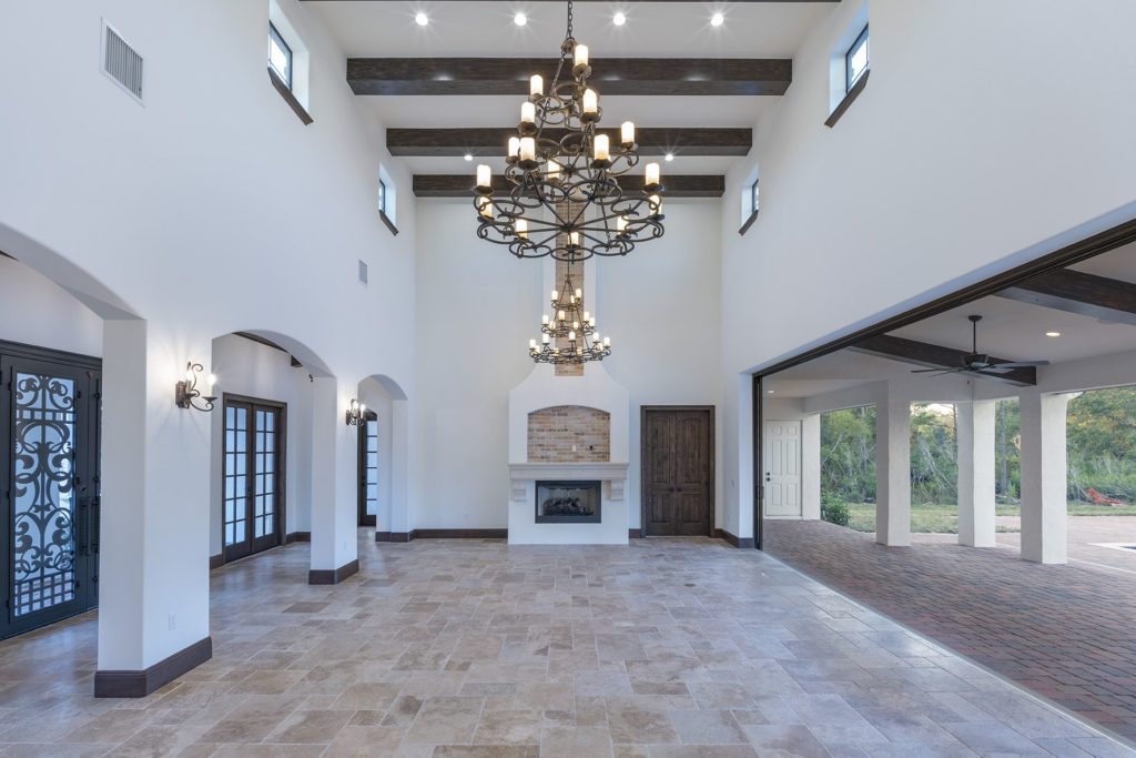 The great room opens to the outdoor living spaces with a 20-foot high ceiling and clerestory windows to draw in natural light from above in this Spanish Revival Custom Home by Orlando Custom Homebuilder Jorge Ulibarri.