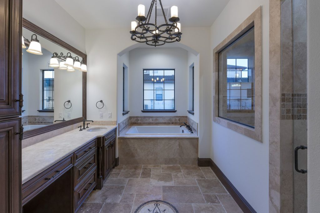 The master bath is clad in travertine stone that compliments the home's flooring.