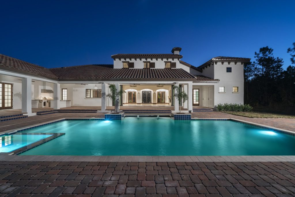 Backyard view of this Spanish Revival custom home by Orlando Custom Homebuilder Jorge Ulibarri that wraps around a pool, spa, outdoor kitchen and living spaces.