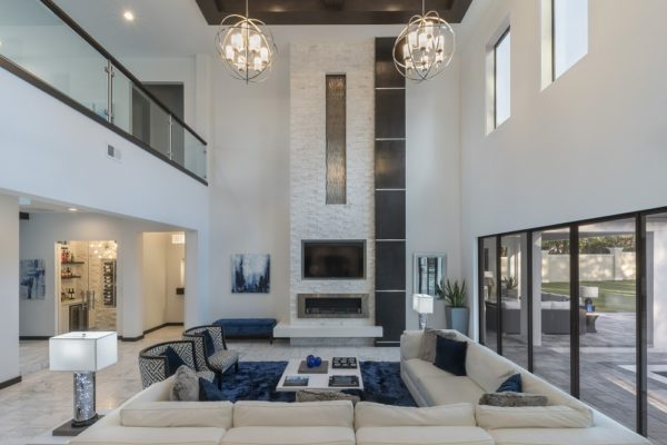 living room of luxury home, sectional couch, blue rug, fireplace