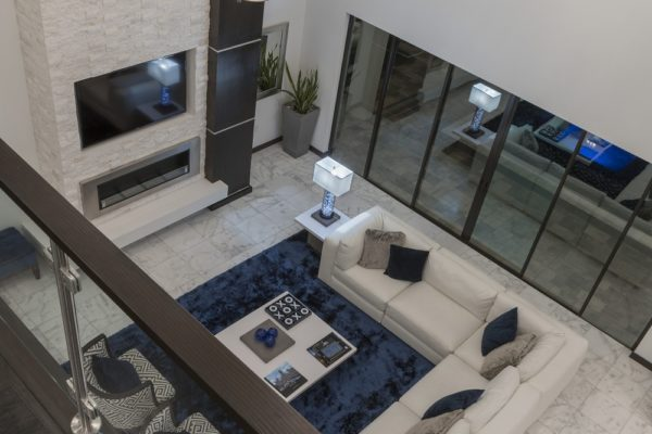 looking down from balcony living room of luxury home, sectional couch, blue rug, fireplace