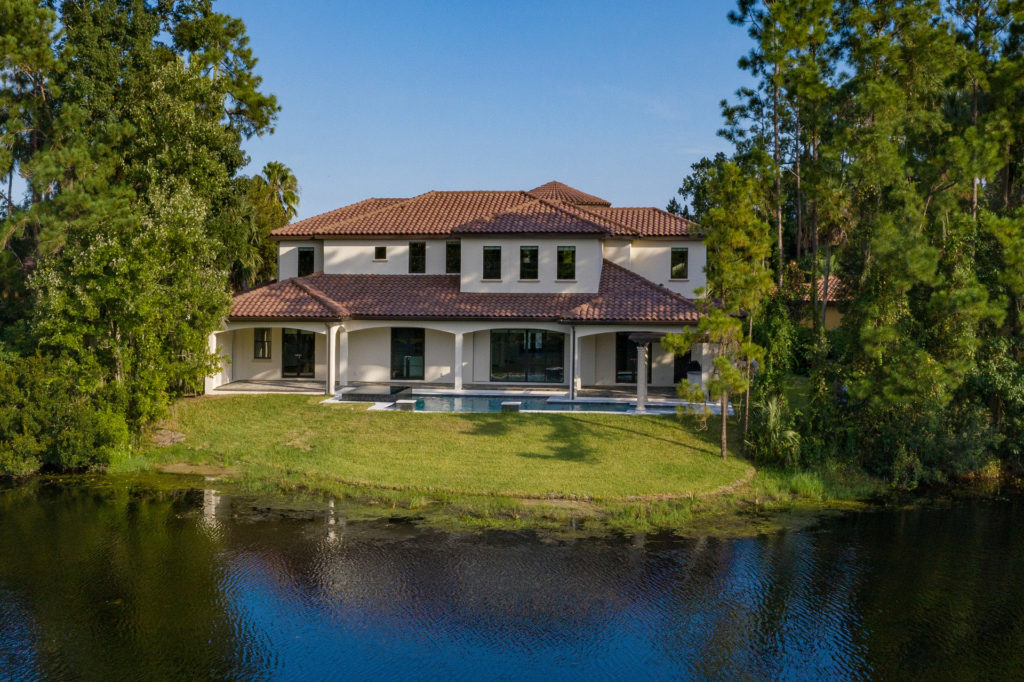 The view from the back of this 5,700 square foot home by Orlando Custom Homebuilder Jorge Ulibarri. The home resides on a half-acre lot with plenty of green spaces for privacy and opens to views of the lake.