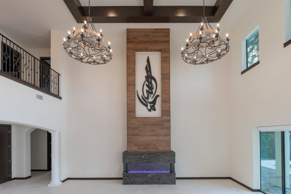 The great room draws focus to an electric fireplace clad in gray stacked stone with a wood plank column that rises above it with an inset to display artwork. The ceilings soar to 22 feet in the great room. The home is designed and built by Orlando Custom Homebuilder Jorge Ulibarri.
