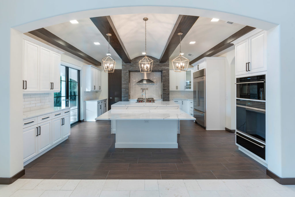 The open kitchen is sleek with white cabinets and quartz counter tops grounded with wood elements including the ceiling beams and the porcelain wood plank floors.