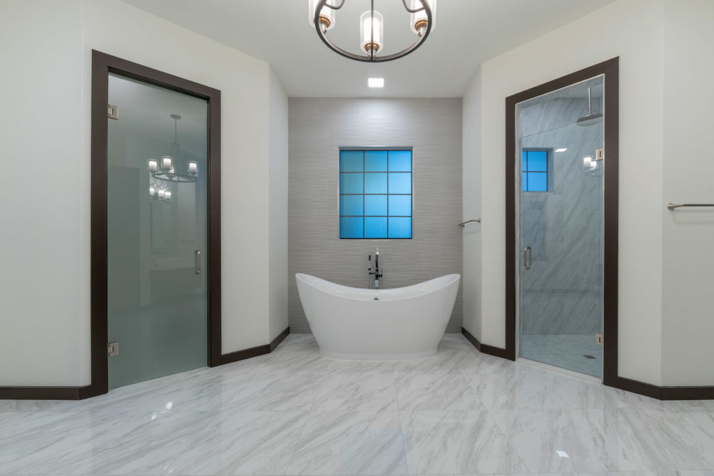 The master bathroom features porcelain tile floors that mimic the look of marble with a niche that frames a free standing tub.