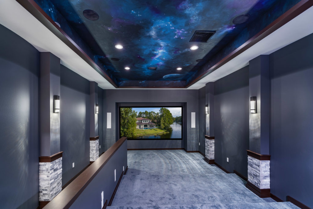 The Theater room upstairs showcases a space mural painted on the ceiling with espresso wood trim, dark gray walls and light gray carpet to create the perfect acoustic conditions and ambiance for watching movies on the large screen.