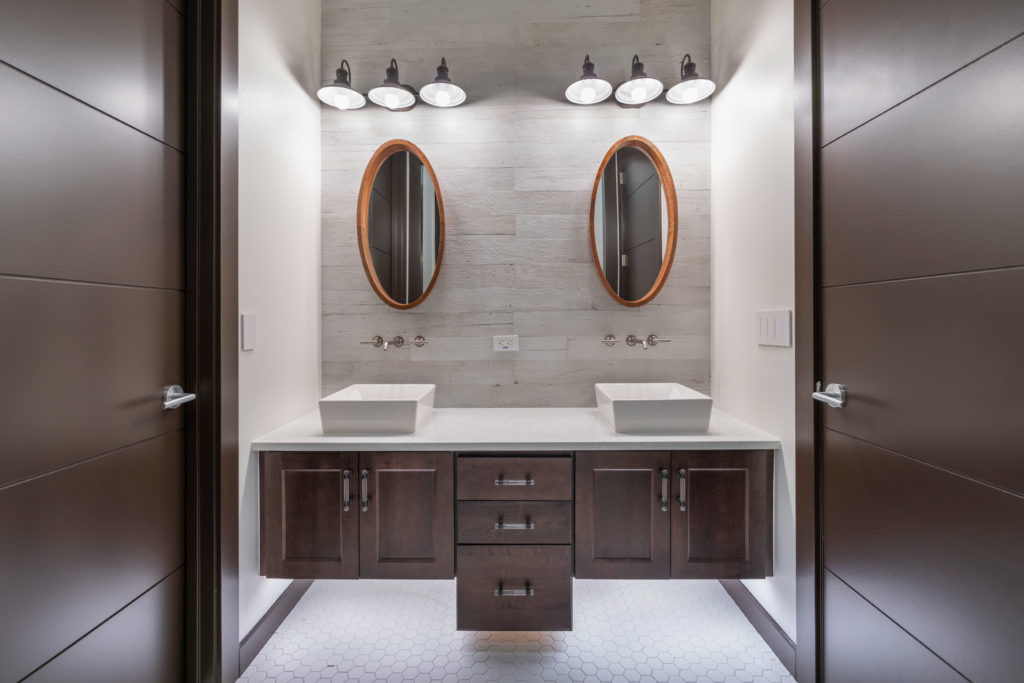 This bathroom conveys a more rustic vibe with its industrial style lighting fixtures and distressed porcelain gray wood plank accent wall behind the vanities with porcelain octagon mosaic tile floors.