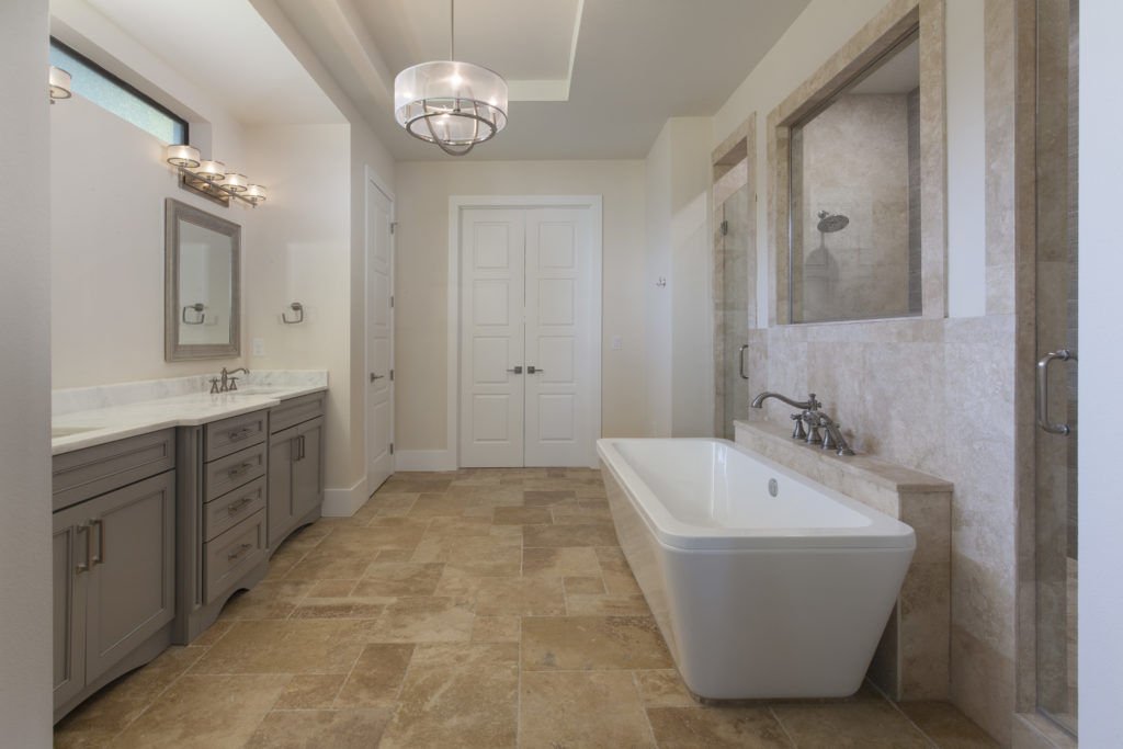 This bathroom by Orlando Custom Home Builder Jorge Ulibarri is illuminated with two vanity light fixtures and a transitional style chandelier.